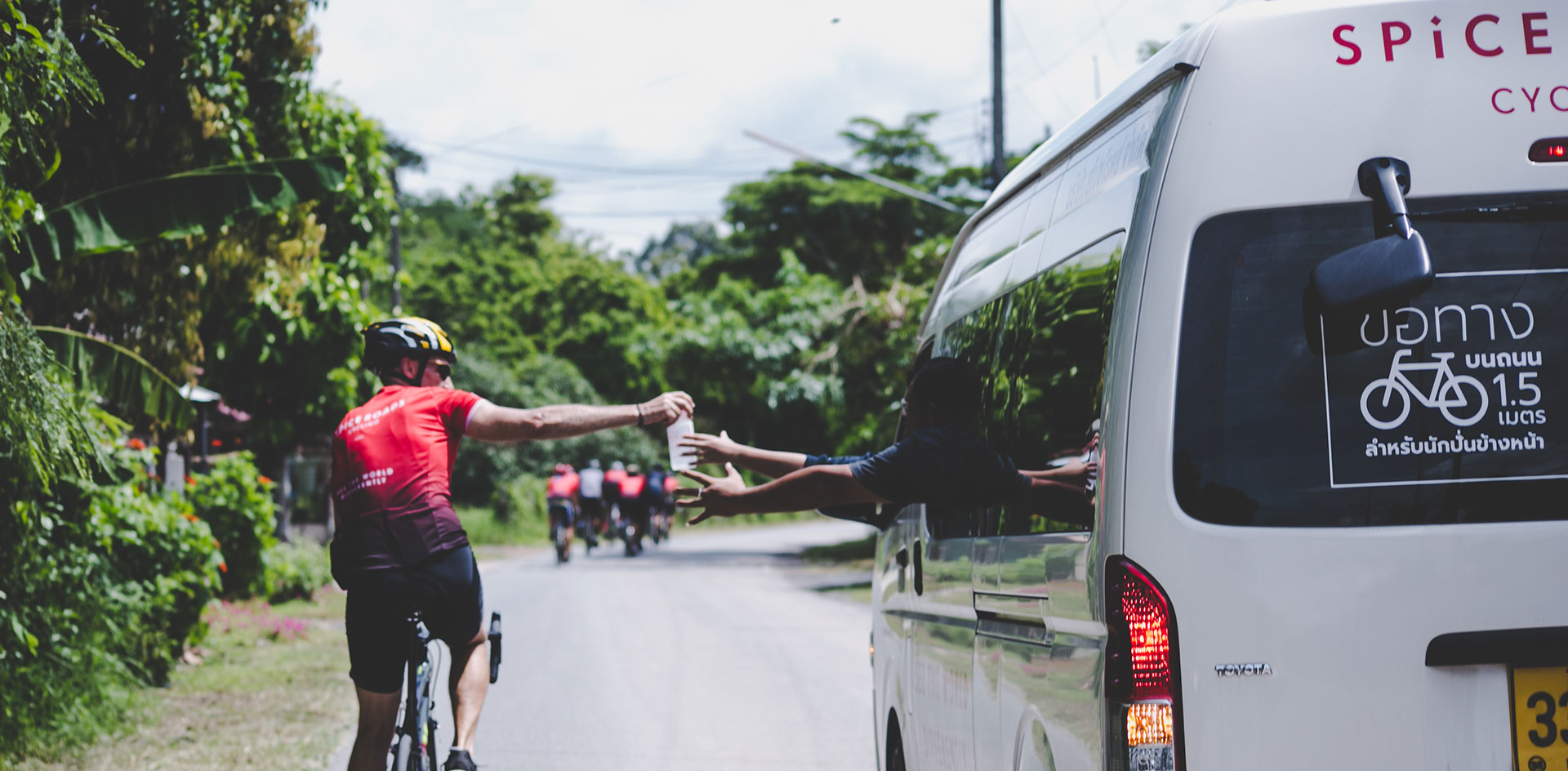 Cycling tour rider getting a water bottle from the support van