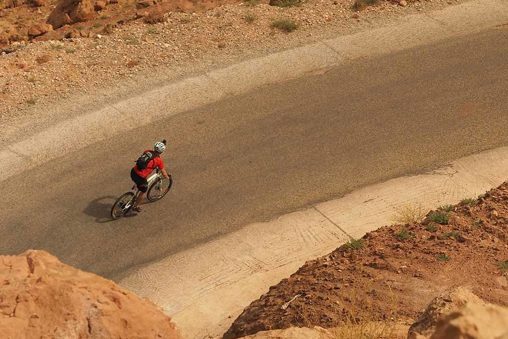 Cyclist riding on track with steep uphill in Morocco