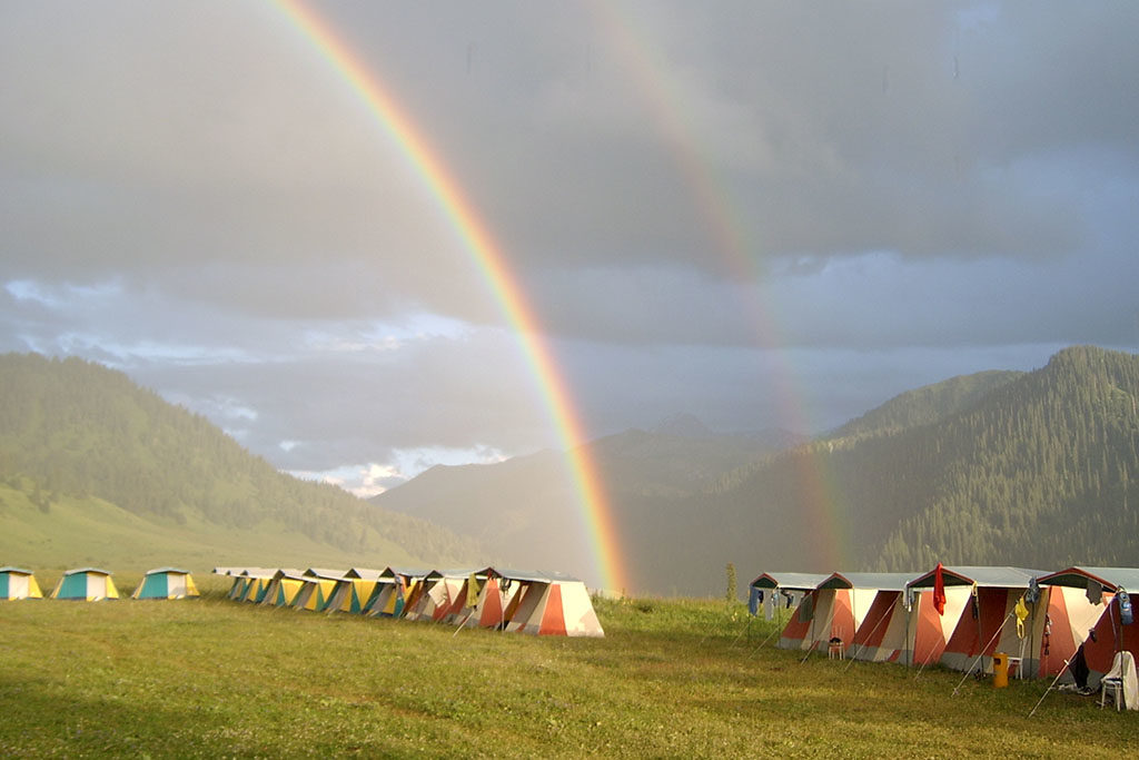 camping tents on Kazakhstan's valleys with lush pastures under the double rainbow
