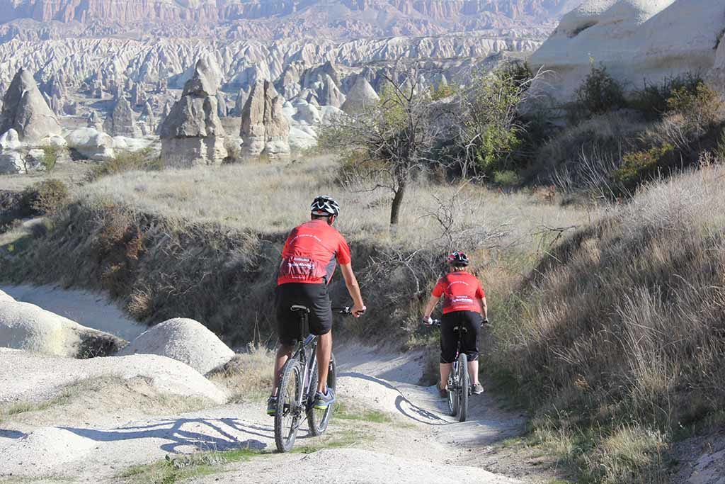 Cyclists riding along the hills and valleys of Cappadocia, Turkey